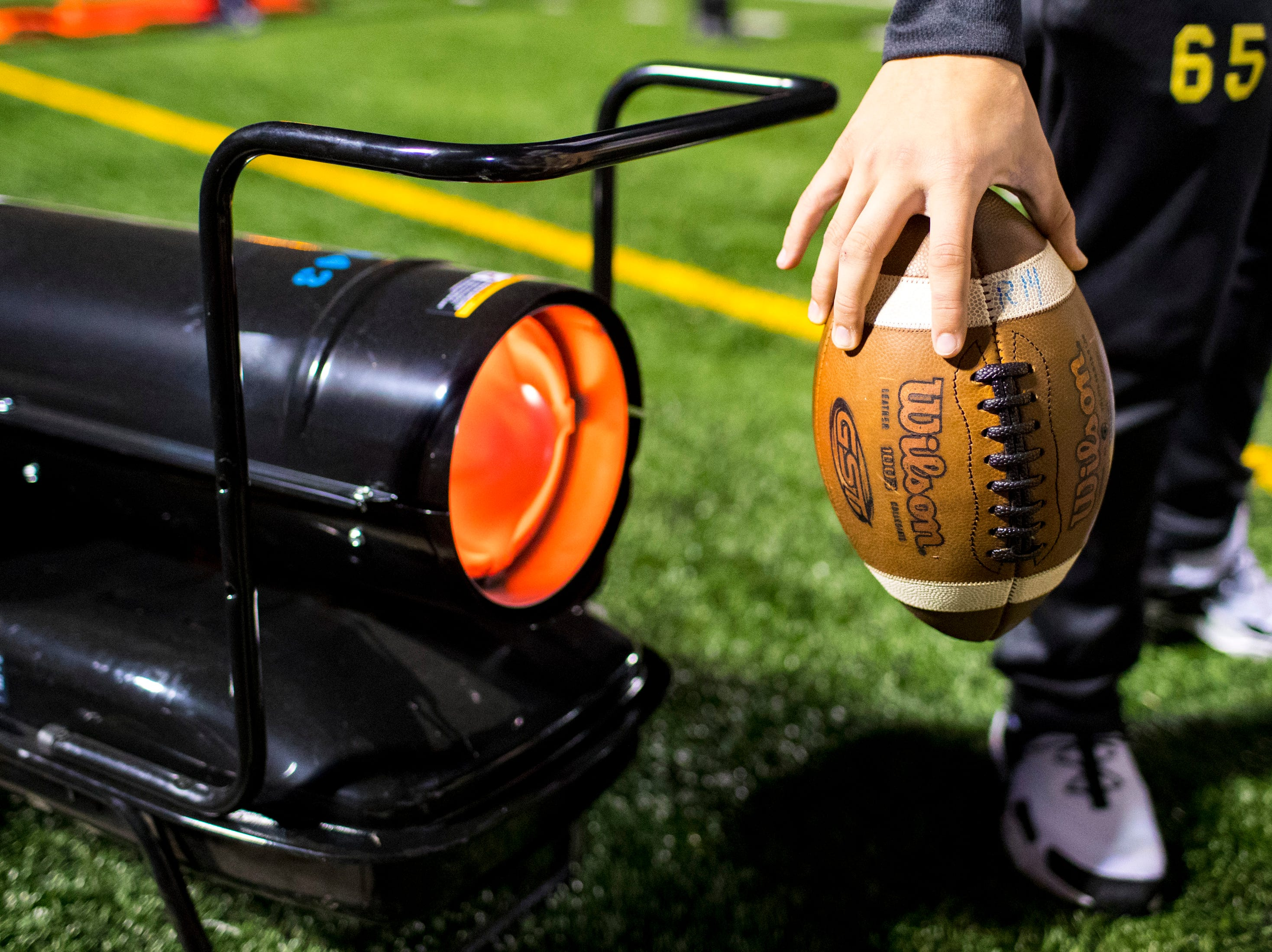 A football is warmed by a portable heater during Brentwood's game against Ravenwood at Brentwood High School in Brentwood on Friday, Nov. 16, 2018.
