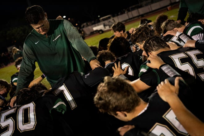 St. John Neumann High School football coach Damon Jones prays with his team after a phenomenal win against the Glades Day School on Friday.