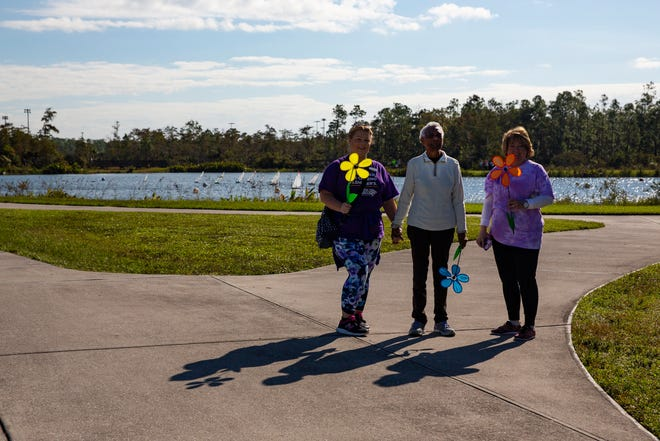 On left, Kaitlin Labadie and Pollie Little, on right, of Inspired Living - a senior assisted living and memory care facility in Bonita Springs - stand with resident and Alzheimer's patient Dorothy Moon as they wait for their other group members to join them in finishing the walk to end Alzheimer's walk, Saturday morning, Nov. 16, 2018 at North Collier Regional Park.