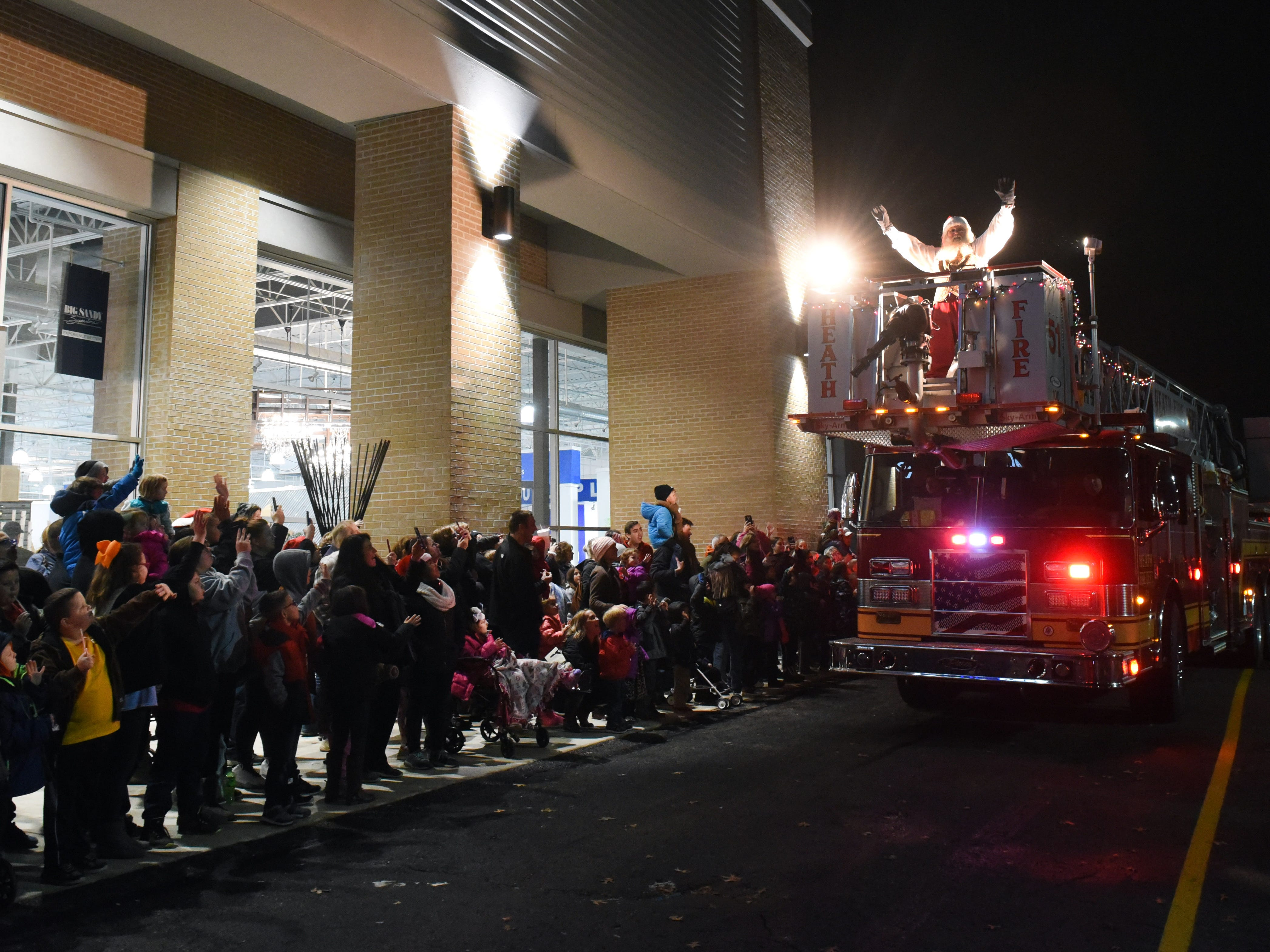 Children line up outside of Big Sandy Superstore to great Santa Claus as he arrives at the Indian Mound Mall with help from Heath Fire Department Tower 51 on Friday, Nov. 16, 2018.