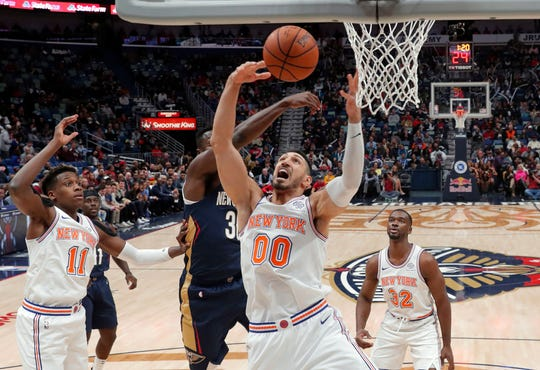 New York Knicks center Enes Kanter (00) battles under the basket with New Orleans Pelicans forward Julius Randle in the first half of an NBA basketball game in New Orleans, Friday, Nov. 16, 2018.