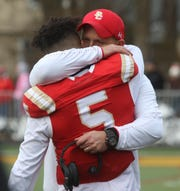 Josh McKenzie of Bergen Catholic is hugged by head coach Vito Campanile towards the end of the game.