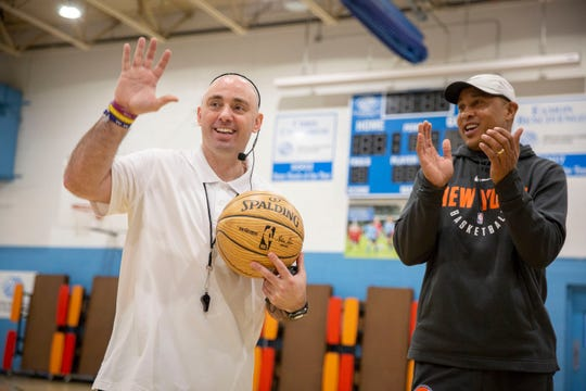 Coach Mike Simmel waves thanks to the crowd with former New York Knick John Starks, at right applauding. Mr Starks surprised Simmel with the with the announcement that he will be presented with the Sweetwater Clifton City Spirit Award at an upcoming Knicks game. during a Bounce Out the Stigma project basketball camp on November 17, 2018 at the Hawthorne Boys and Girls Club in Hawthorne, NJ.