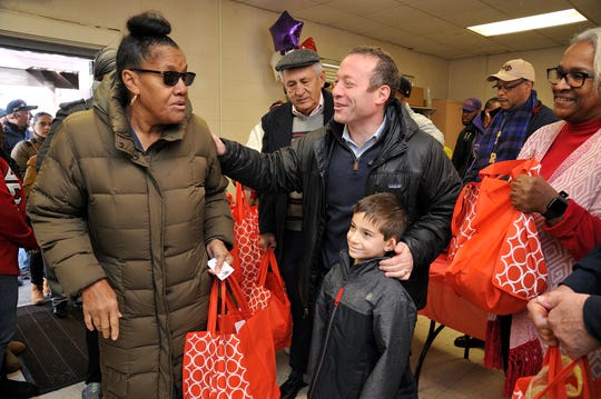 Congressman Josh Gottheimer and his son Ben give a turkey to Hackensack resident Ruth Ann Travis at the second annual Turkey Give-A-Way on Saturday