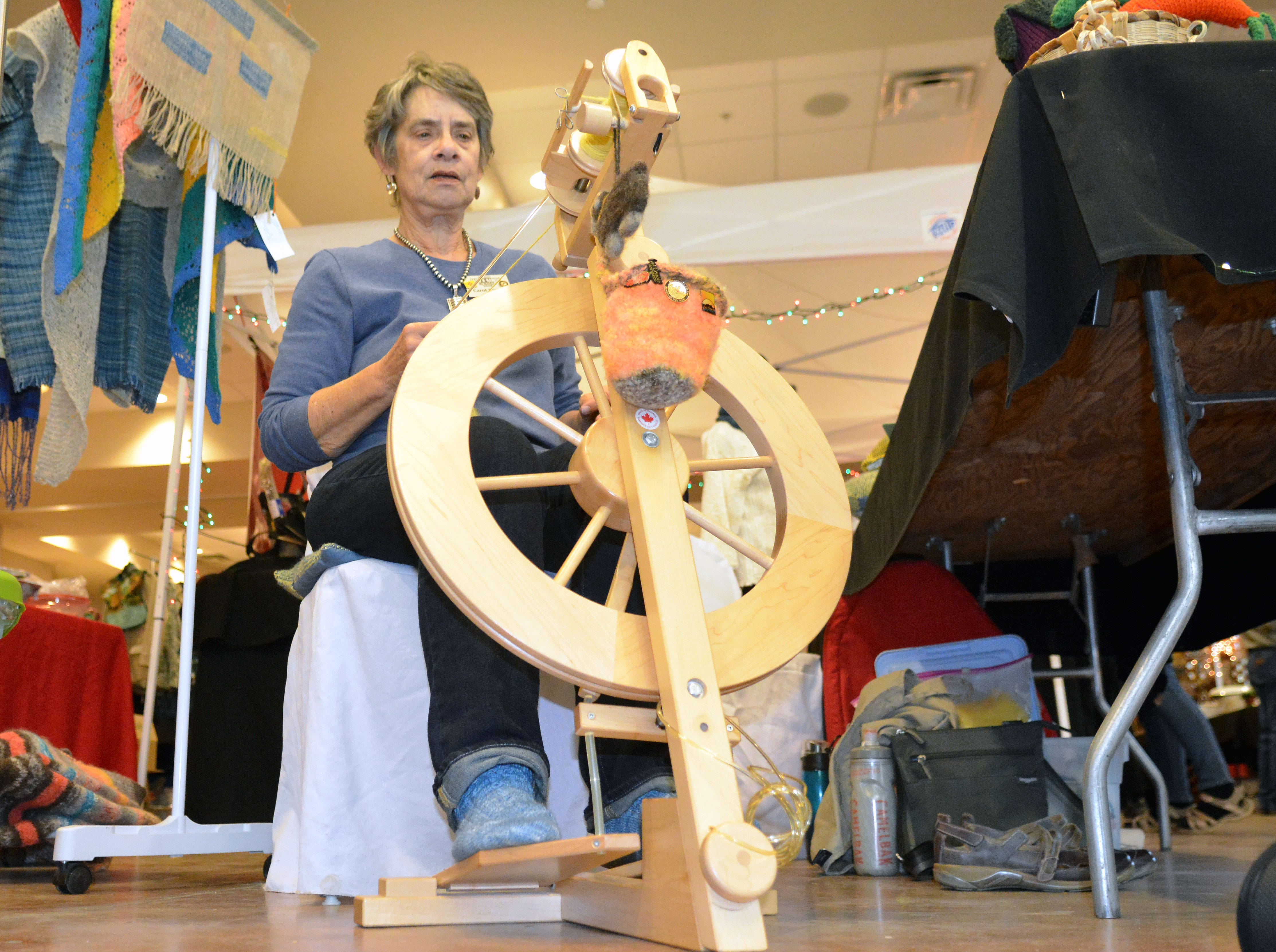 Carol Eggers spins yarn on her spinning wheel, which she then weaves and knits into place mats, scarves and towels.  She was one of more than 70 vendors at this year's HomeGrown Food Show and Gift Market at the Farm and Ranch Heritage Museum.  Photo taken 11/17/18.