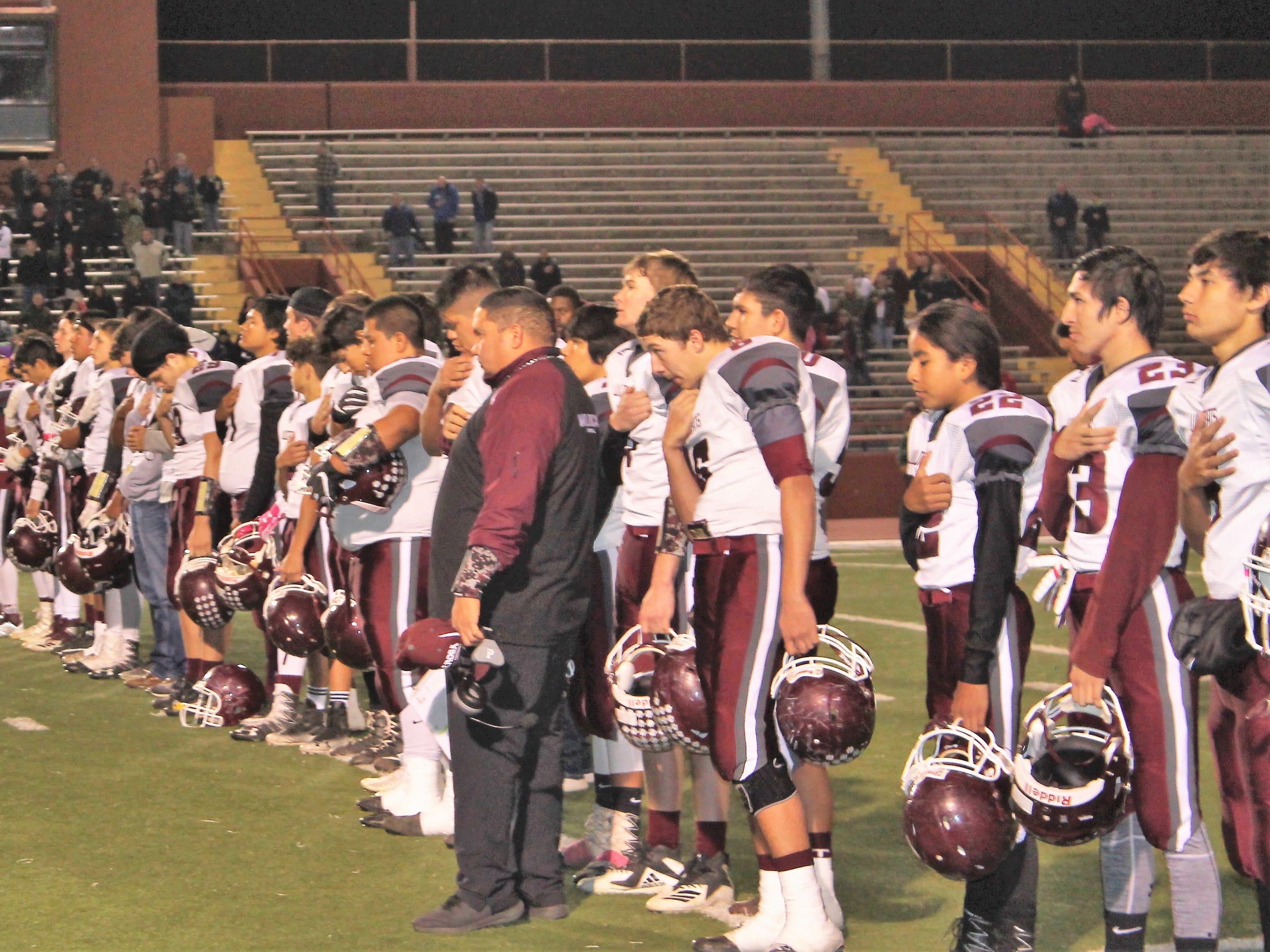 The Tularosa Wildcats salute the American Flag during the National Anthem at Friday night's 3A State Championship Quarterfinal against the Hope Christian Huskies. The Huskies won the game 67-14.