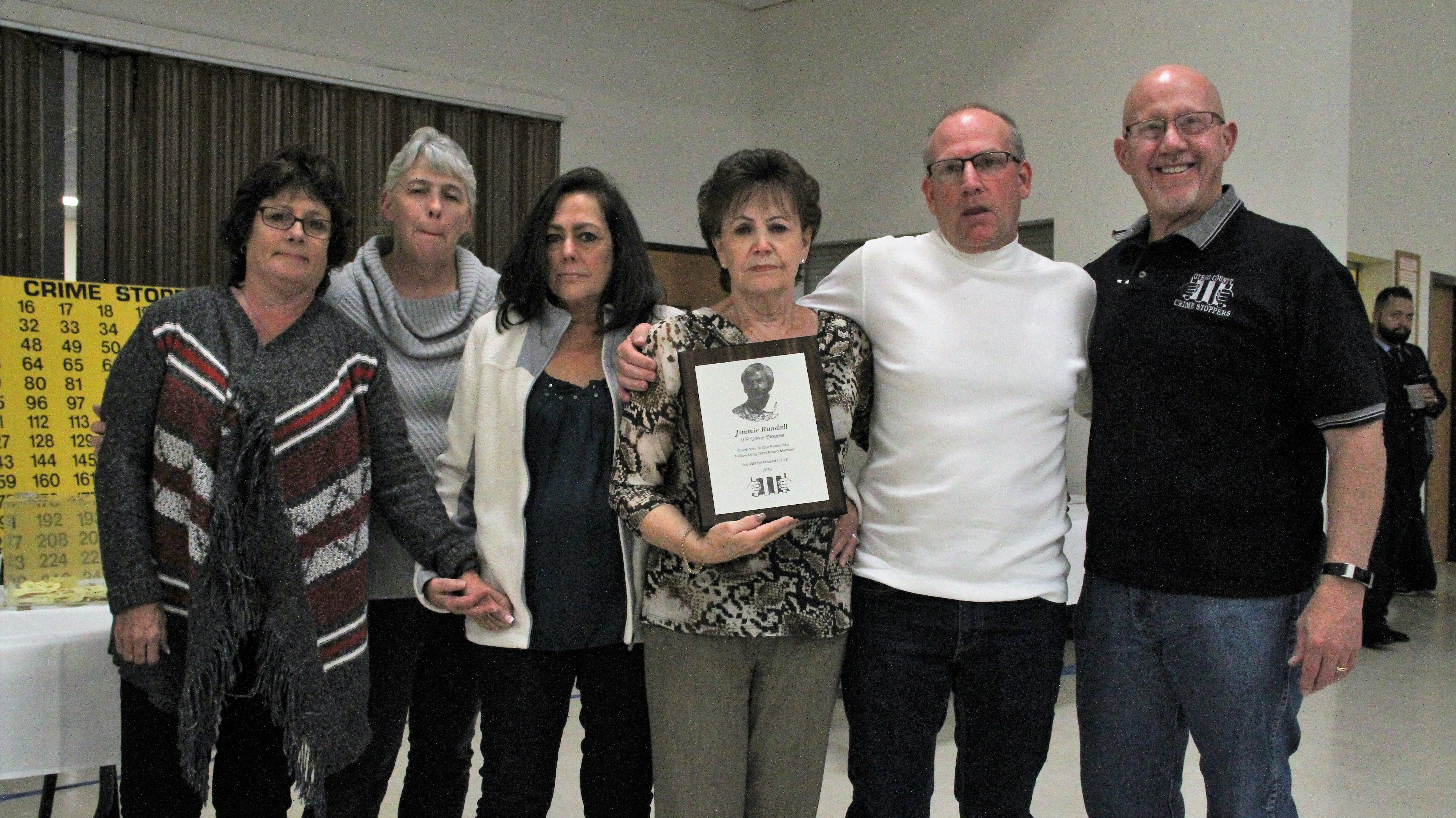 Jimmie Randall's wife, Juanita, center, holds a plaque honoring Jimmie at the Otero County Crime Stoppers fundraiser Oct. 20. Pictured from left to right are Tiffany Carnes, Tonya Sanchez, Cheryl Woods, Juanita,  Tom Thompson and Crime Stopper Board Member Steve Muell.
