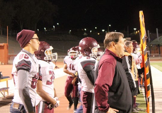 Tularosa Wildcats Coach Richard Grace and team watch the players on the field at the 3A State Championship Quarterfinal against the Hope Christian Huskies on November 16, 2018.