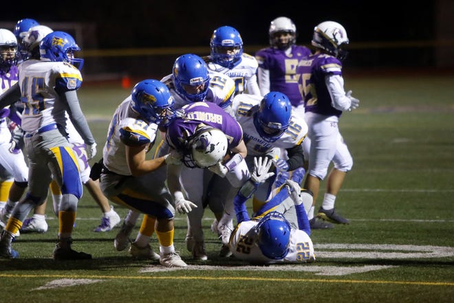 Kirtland Central's Cadan Flack is brought down by Bloomfield defenders JT Seitzinger (27), Vince Marquez (12) and Josh Maestas (16) during Friday's 4A state football quarterfinals at KCHS.