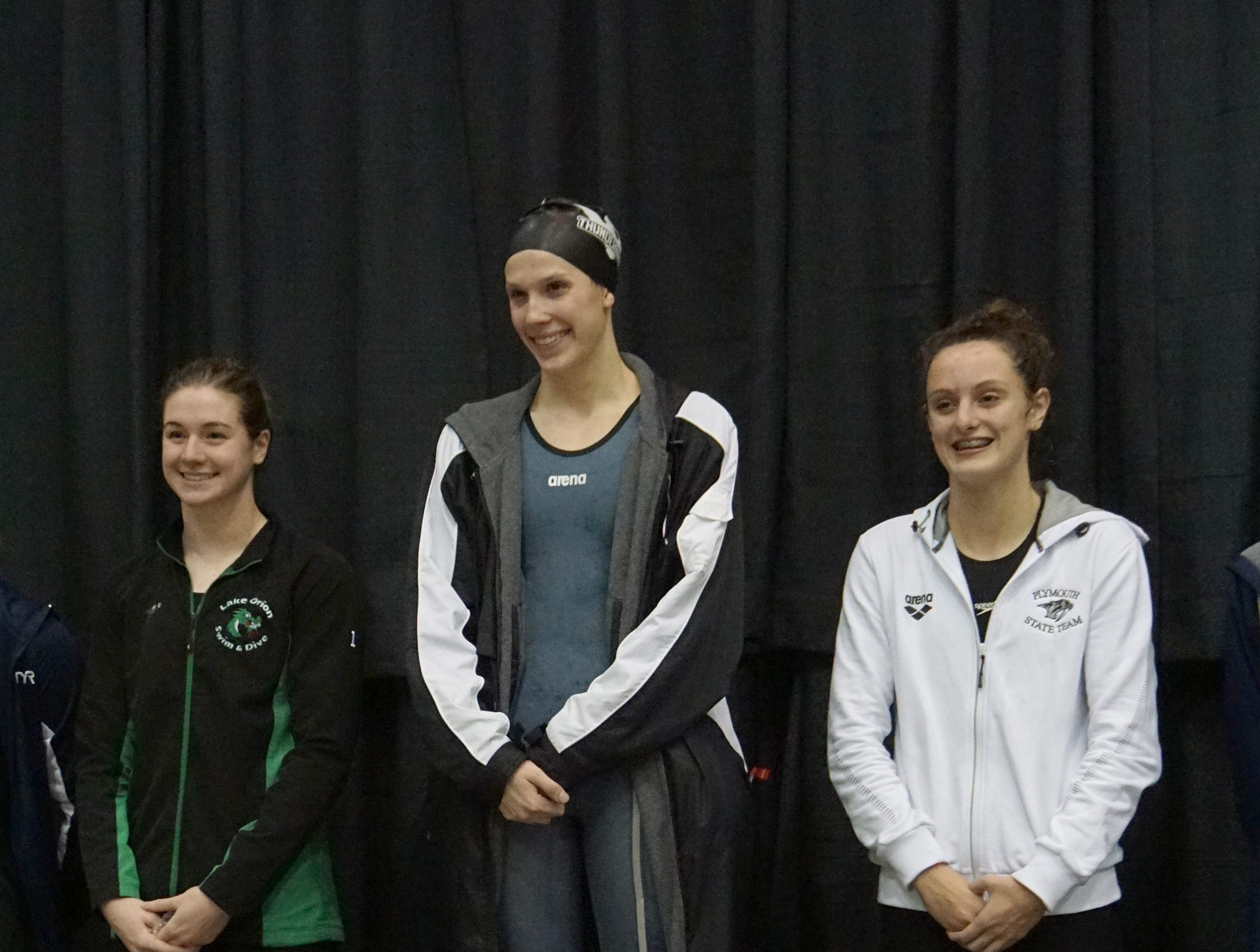 Farmington/Harrison's Ashley turak stands on the podium after winning the 50-yard freestyle at the Division 1 girls swimming and diving championships held at Eastern Michigan University Nov. 17, 2018.
