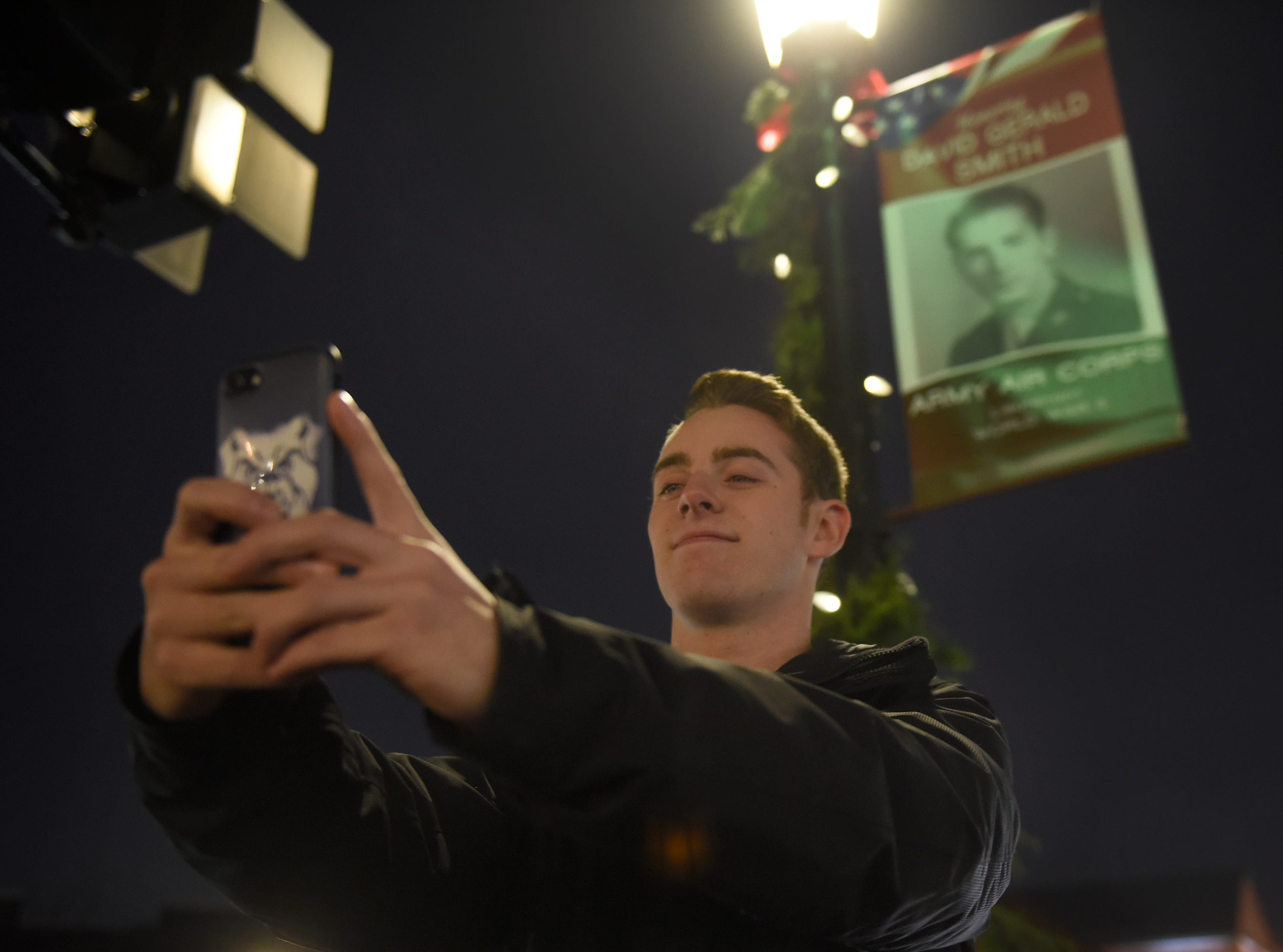 Connor Lepish takes a selfie in front of a banner on Main Street featuring his grandfather before the start of the Holiday Lighted Parade in downtown Northville, Nov. 16, 2018.