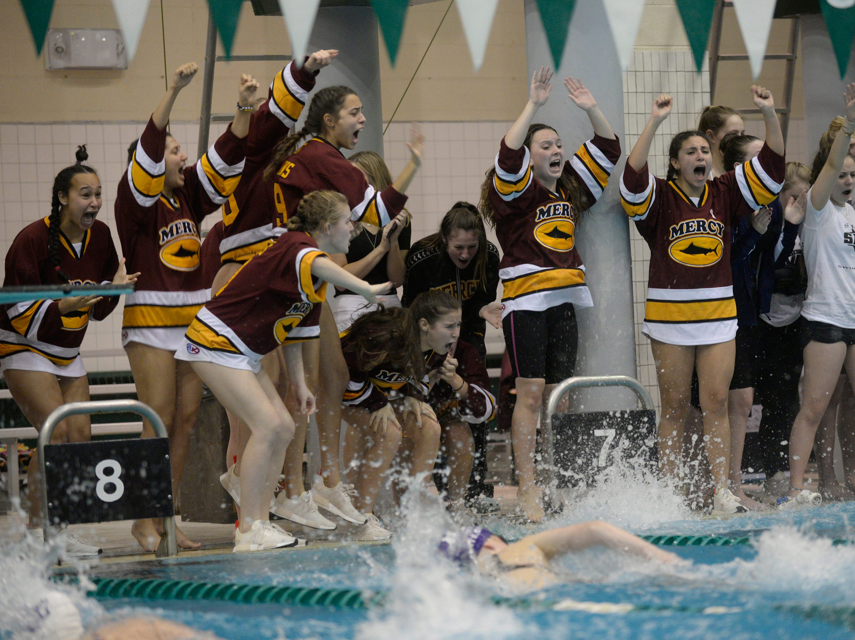 Mercy swimmers cheer on the 400 yard relay team at the Division 1 girls swimming and diving championships held at Eastern Michigan University Nov. 17, 2018.