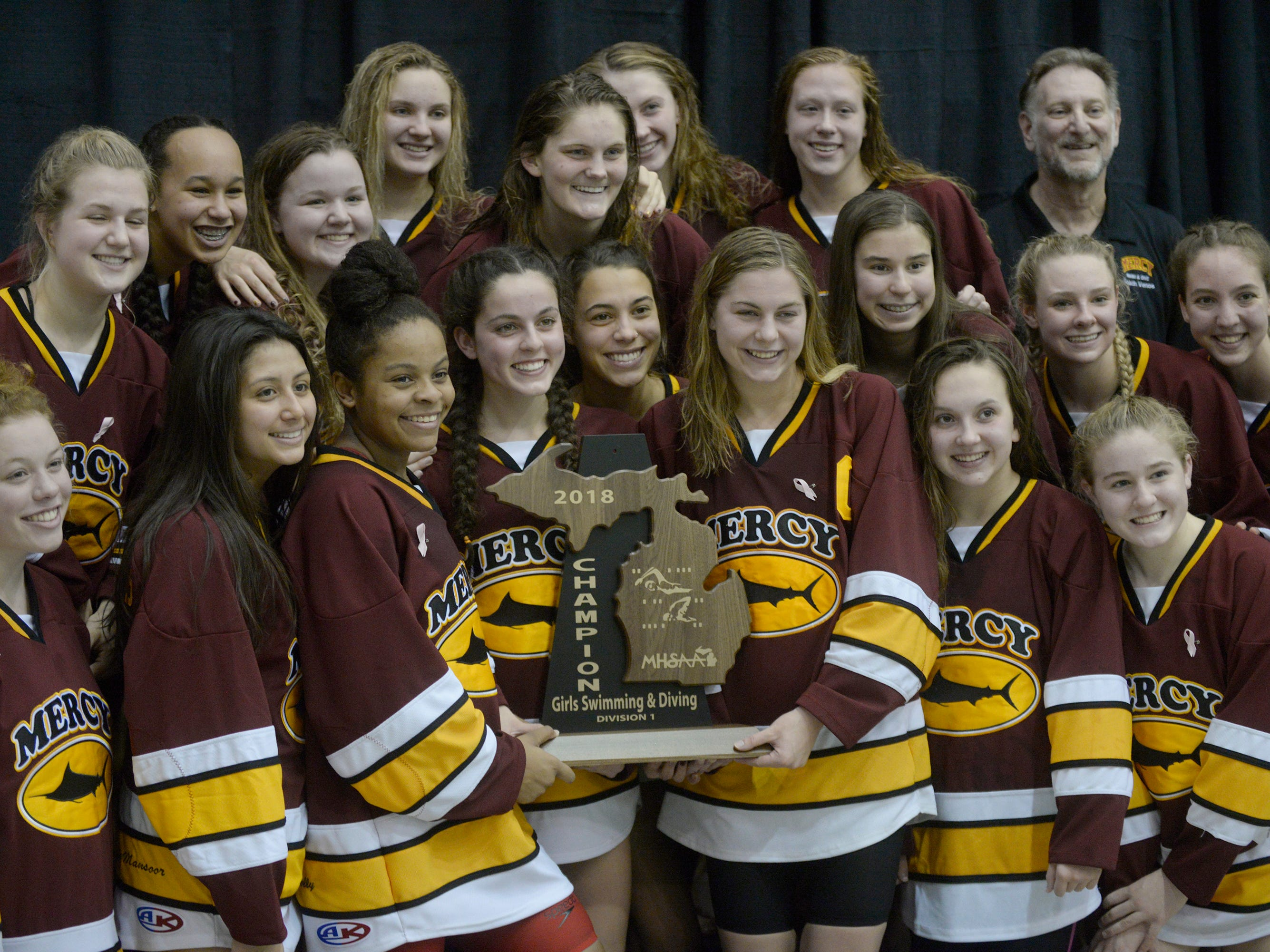 Mercy swimmers pose with the championship trophy at the Division 1 girls swimming and diving championships held at Eastern Michigan University Nov. 17, 2018.