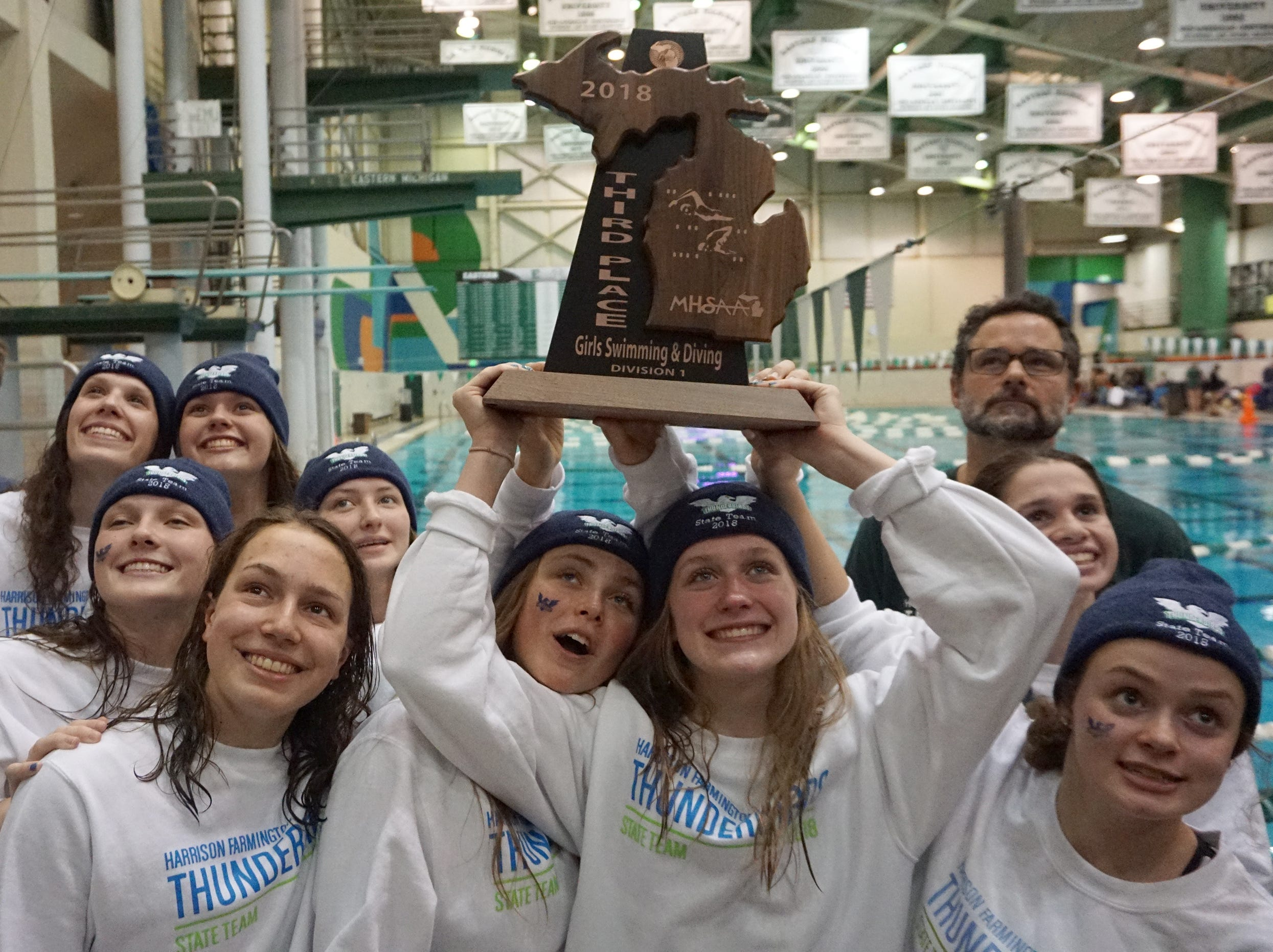 Harrison/Farmington swimmers hold the third place trophy at the Division 1 girls swimming and diving championships held at Eastern Michigan University Nov. 17, 2018.