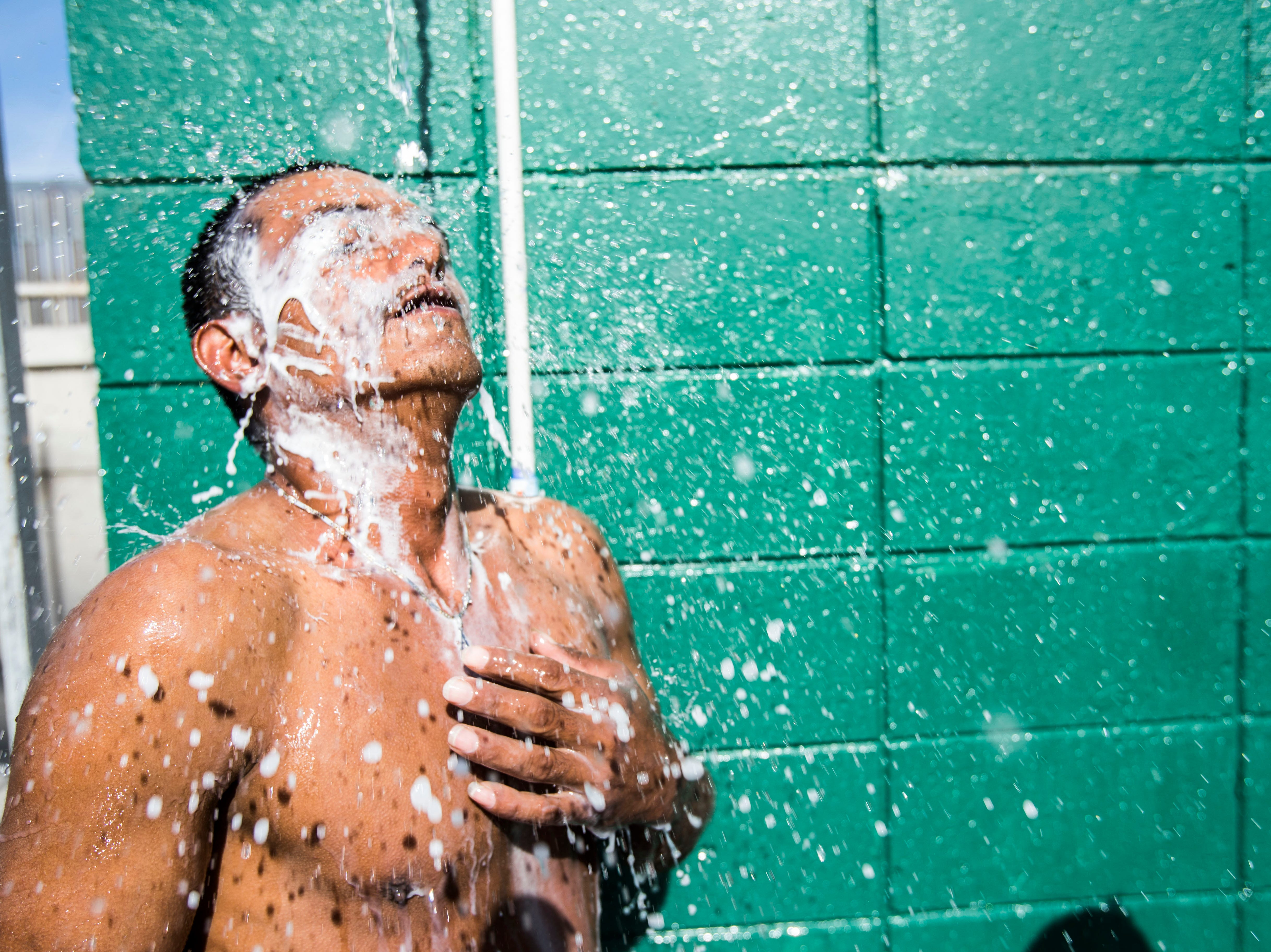 Migrants who had not bathe in days quickly take advantage of water running through makeshift pipes in the Benito Juarez sports complex in Tijuana, Mexico.