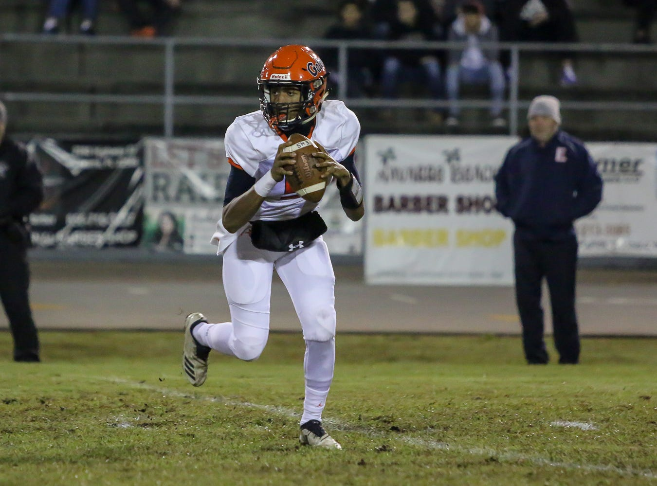 Escambia quarterback AV Smith (5) rolls to his left and looks for a receiver to pass to against the Raiders in the Region 1-6A Semifinal game at Navarre High School on Friday, November 16, 2018.
