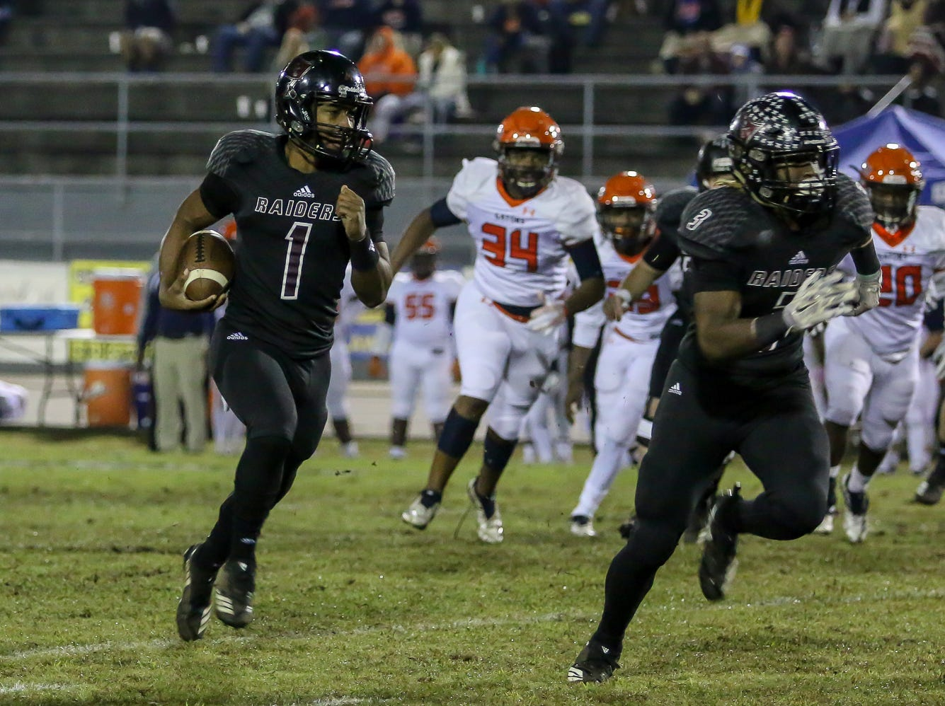 Navarre quarterback Marlon Courtney III (1) follows his lead blocker, Christopher Williams (3), and runs in for a 15-yard touchdown on the Raiders' first play against Escambia in the Region 1-6A Semifinal game at Navarre High School on Friday, November 16, 2018.