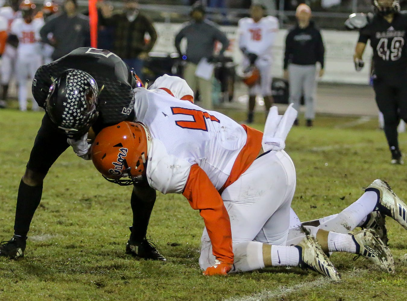 Escambia's Noah Lord (4) goes down lie to stop Navarre's Dante Wright (5) in the Region 1-6A Semifinal game at Navarre High School on Friday, November 16, 2018.