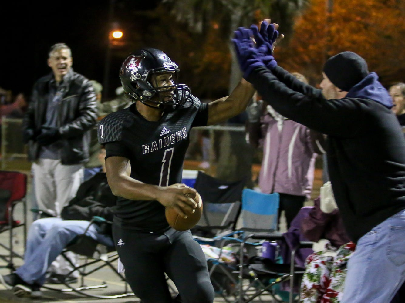 Navarre quarterback Marlon Courtney III (1) celebrates after a 15-yard touchdown run on the Raiders' first play against Escambia in the Region 1-6A Semifinal game at Navarre High School on Friday, November 16, 2018.