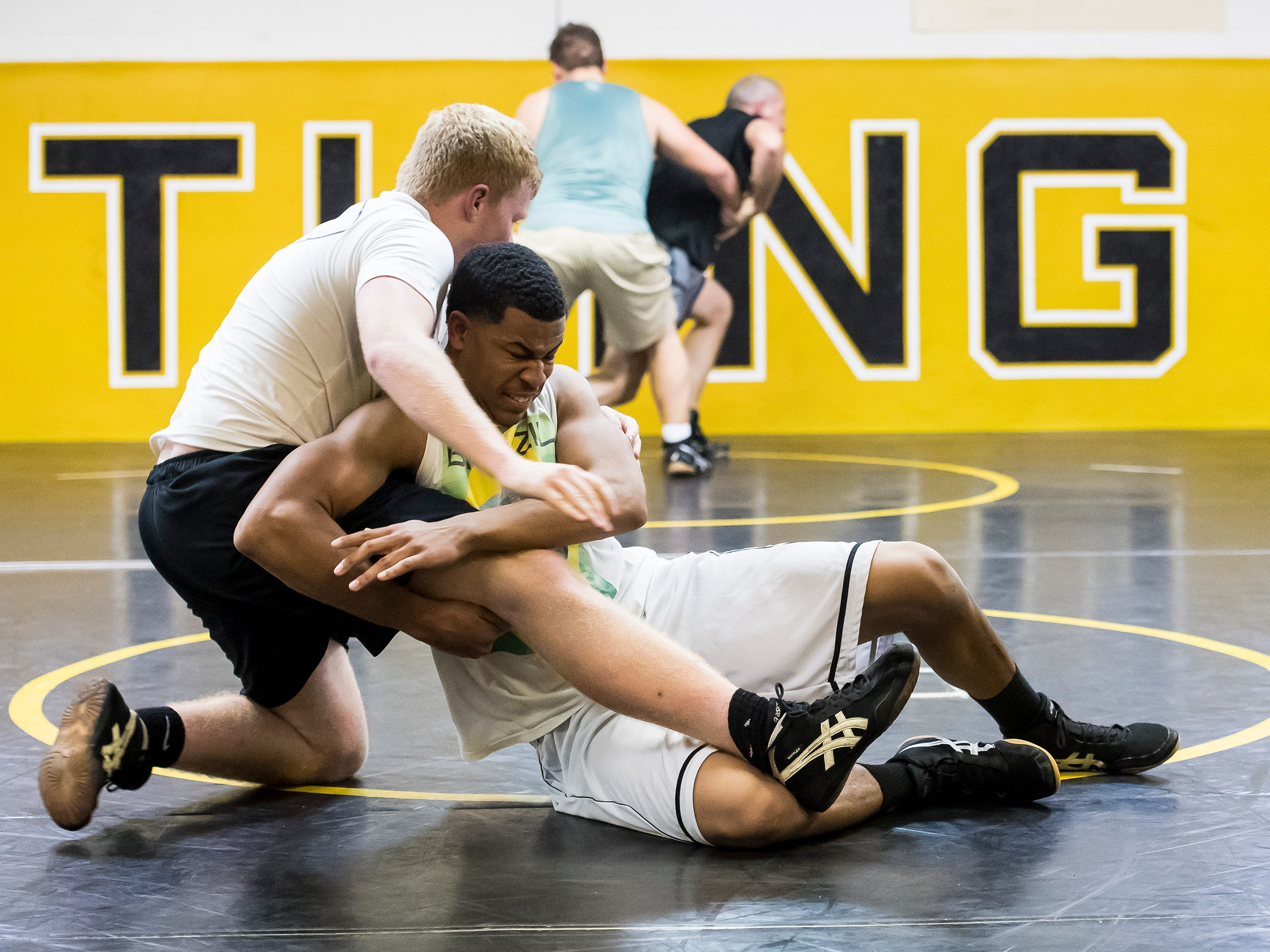 Delon Catholic's Marquise Suite, bottom, wrestles Collin Snyder during the first official day of winter sports practice on Friday, November 16, 2018.