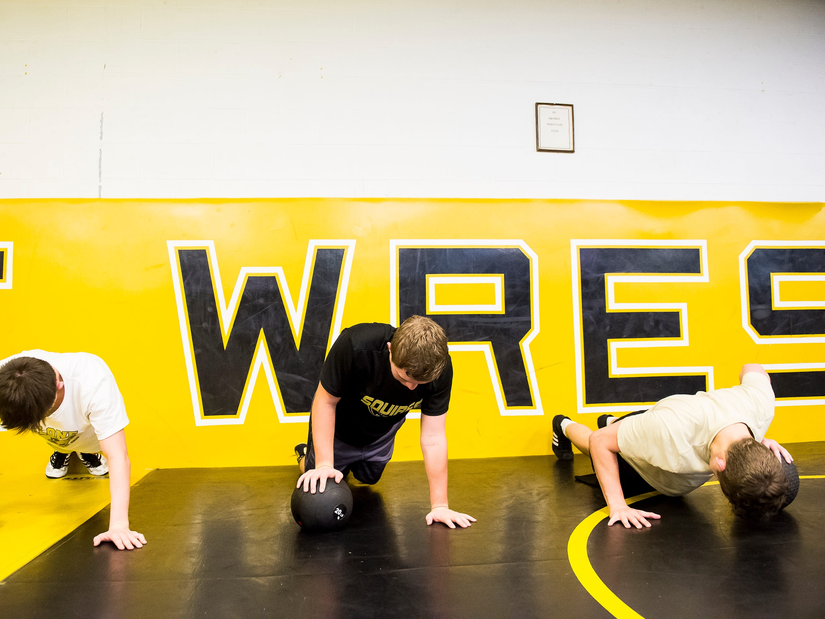 Delon Catholic wrestlers do one arm push-ups during the first official day of winter sports practice on Friday, November 16, 2018.