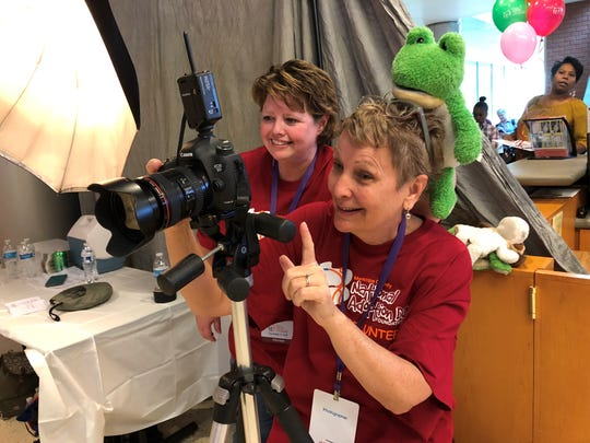 Assistant Sam Kaufman plops a stuffed frog on top of photographer Patty Kaufman's head to make the kids laugh while she took family portraits for Maricopa County's National Adoption Day on Nov. 17, 2018.