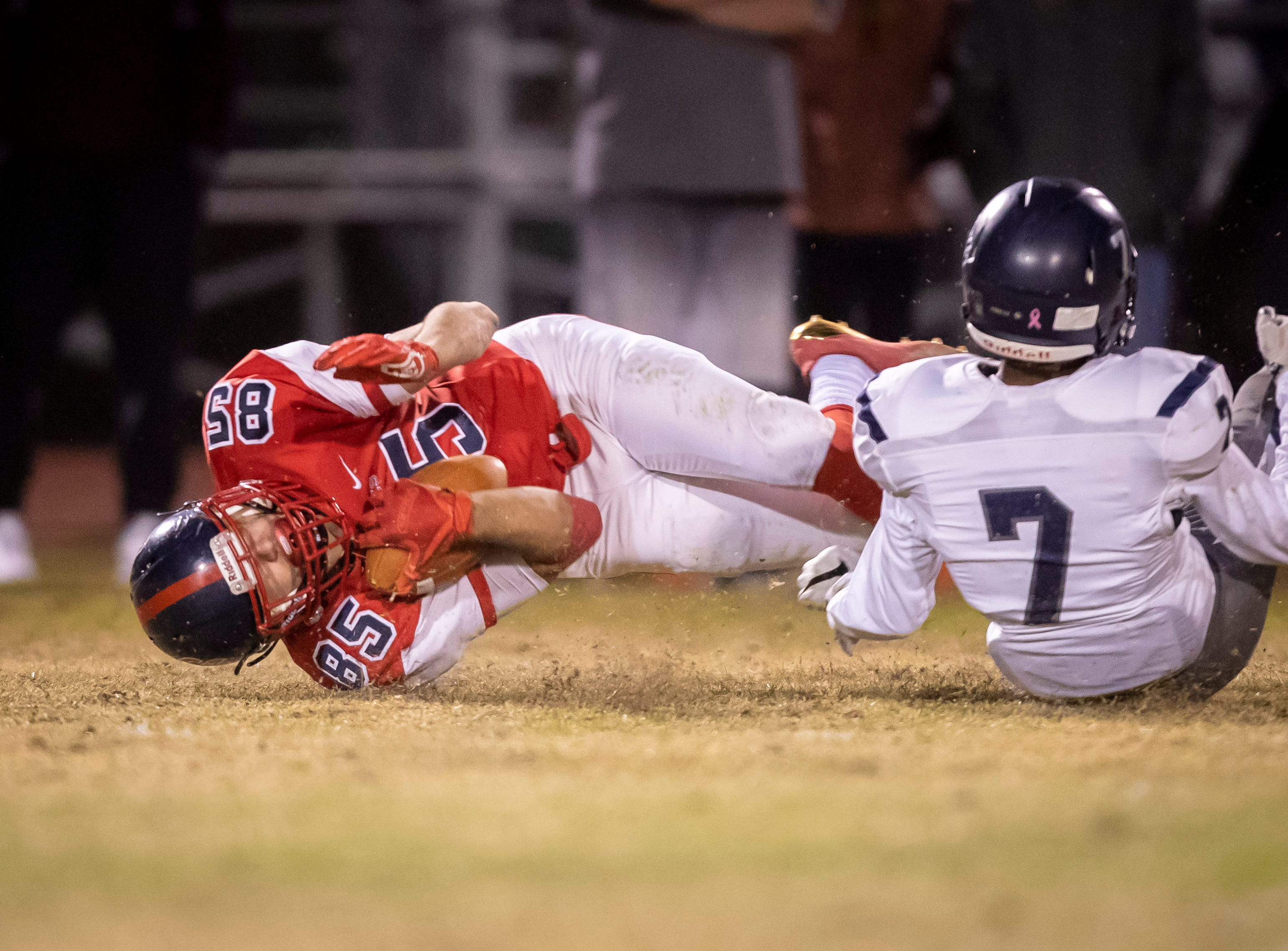 Runner Brad Young (85) of the Centennial Coyotes is brought down by junior free safety Elijah Taylor (7) of the Higley Knights in the 5A semi-finals at Willow Canyon High School on Friday, November 16, 2018 in Surprise, Arizona. #azhsfb