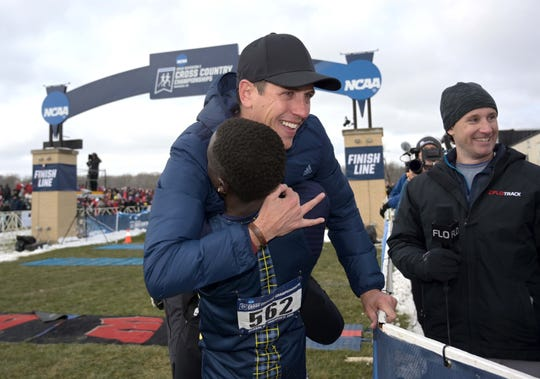 Northern Arizona coach Michael Smith celebrates with Peter Lomong (562) after the Lumberjacks won the team title for the third year in a row during the NCAA Cross Country Championships Saturday at the Thomas Zimmer Championship Course in Madison, Wis.  Kirby Lee-USA TODAY Sports
