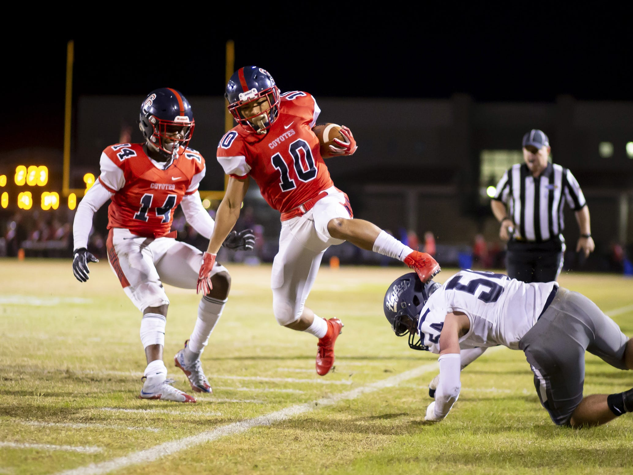 Senior wide receiver Jeiel Stark (10) of the Centennial Coyotes is pulled out of bounds by senior middle linebacker Dylan Pedersen (54) of the Higley Knights in the playoffs at Willow Canyon High School on Friday, November 16, 2018 in Surprise, Arizona. #azhsfb