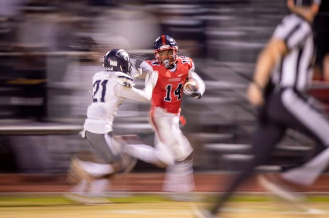 Junior wide receiver Dyelan Miller (14) of the Centennial Coyotes runs the ball against junior cornerback Brail Lipford (21) of the Higley Knights in the 5A semi-finals at Willow Canyon High School on Friday, November 16, 2018 in Surprise, Arizona. #azhsfb