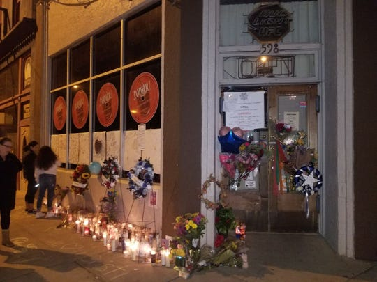 People pay their respects at Jammerz bar, where three people were fatally shot and one person was injured Sunday evening.