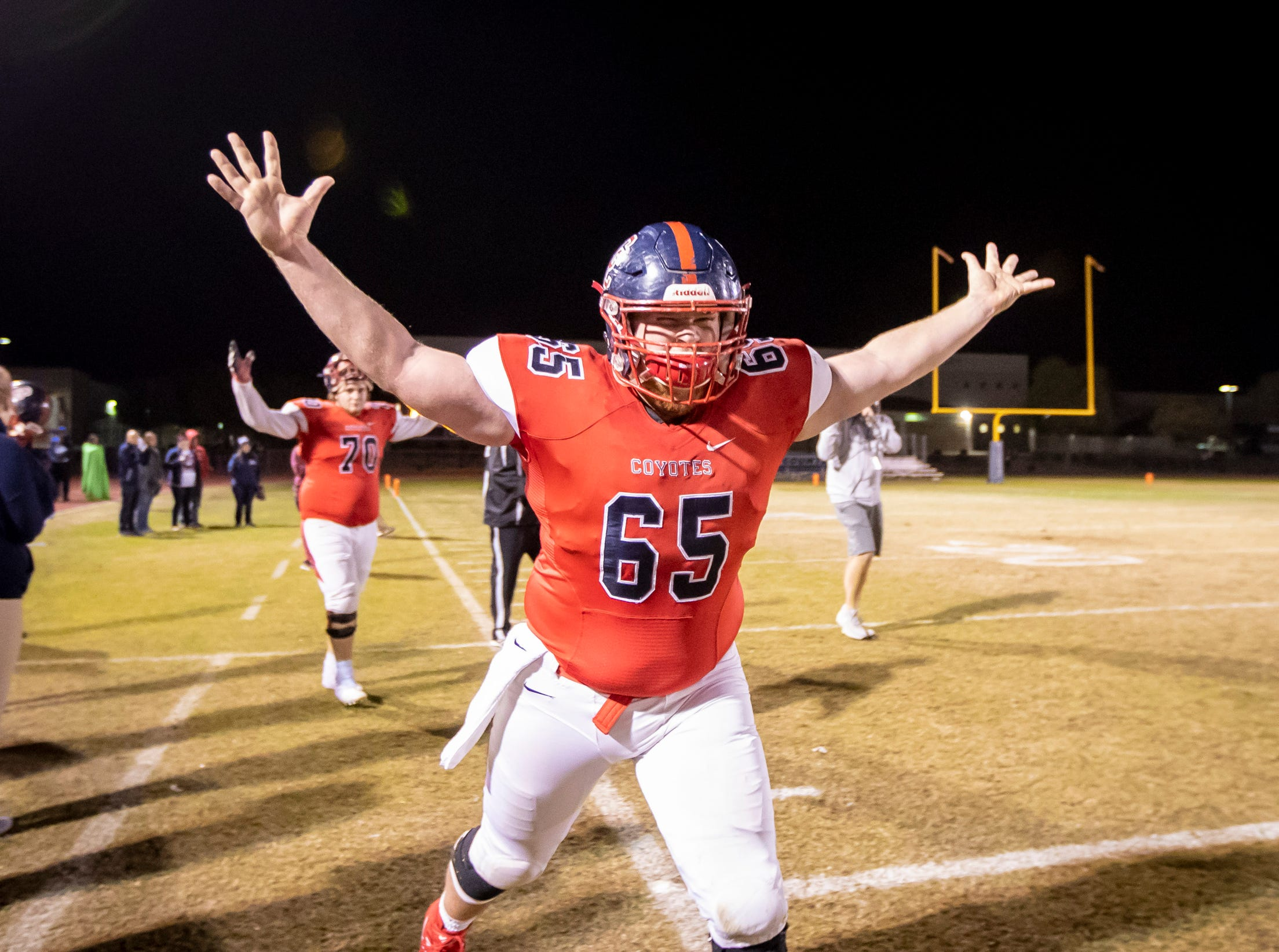 Senior center Carson Keltner (65) of the Centennial Coyotes celebrates following Centennial's 48-13 win against the Higley Knights in a 5A semifinals at Willow Canyon High School on Friday, November 16, 2018 in Surprise, Arizona. #azhsfb