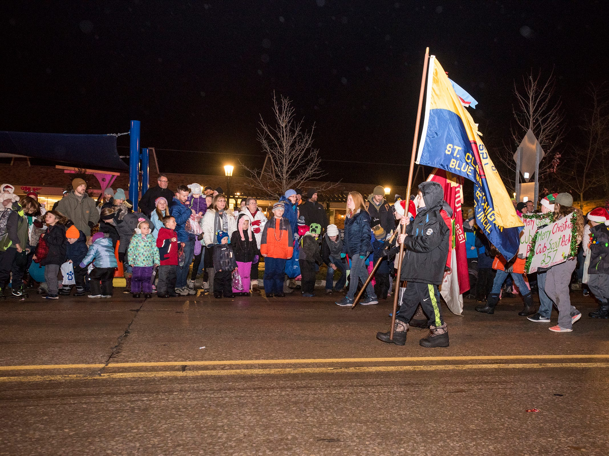 Boy and Cub Scouts march down Riverside Avenue Friday, Nov. 16, 2018 during the St. Clair Lighted Santa Parade.