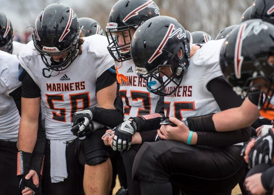 Marine City High School's Josh Headlee (58), Ben Wright (23) and Seth Tackaberry link hands with other teammates after falling to Portland High School 35-14 in the MHSAA Division 5 state football semifinals Saturday, Nov. 17, 2018 at Howell High School.