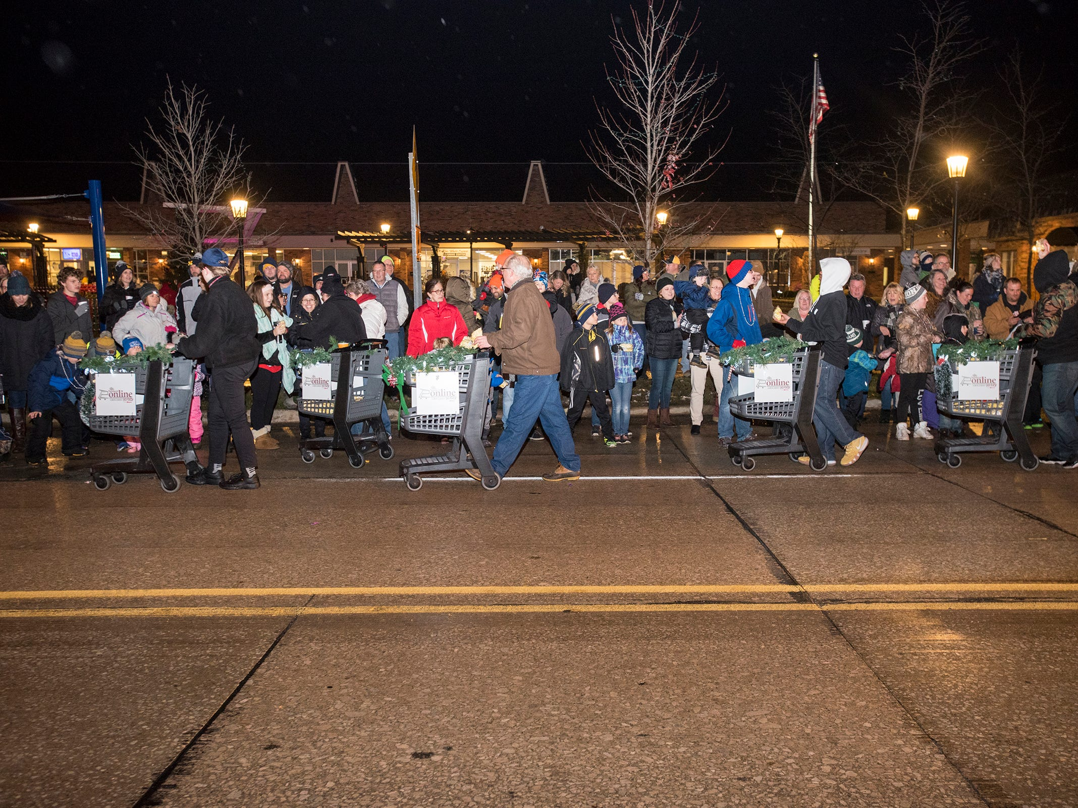 People push illuminated shopping carts down Riverside Avenue Friday, Nov. 16, 2018 during the St. Clair Lighted Santa Parade.