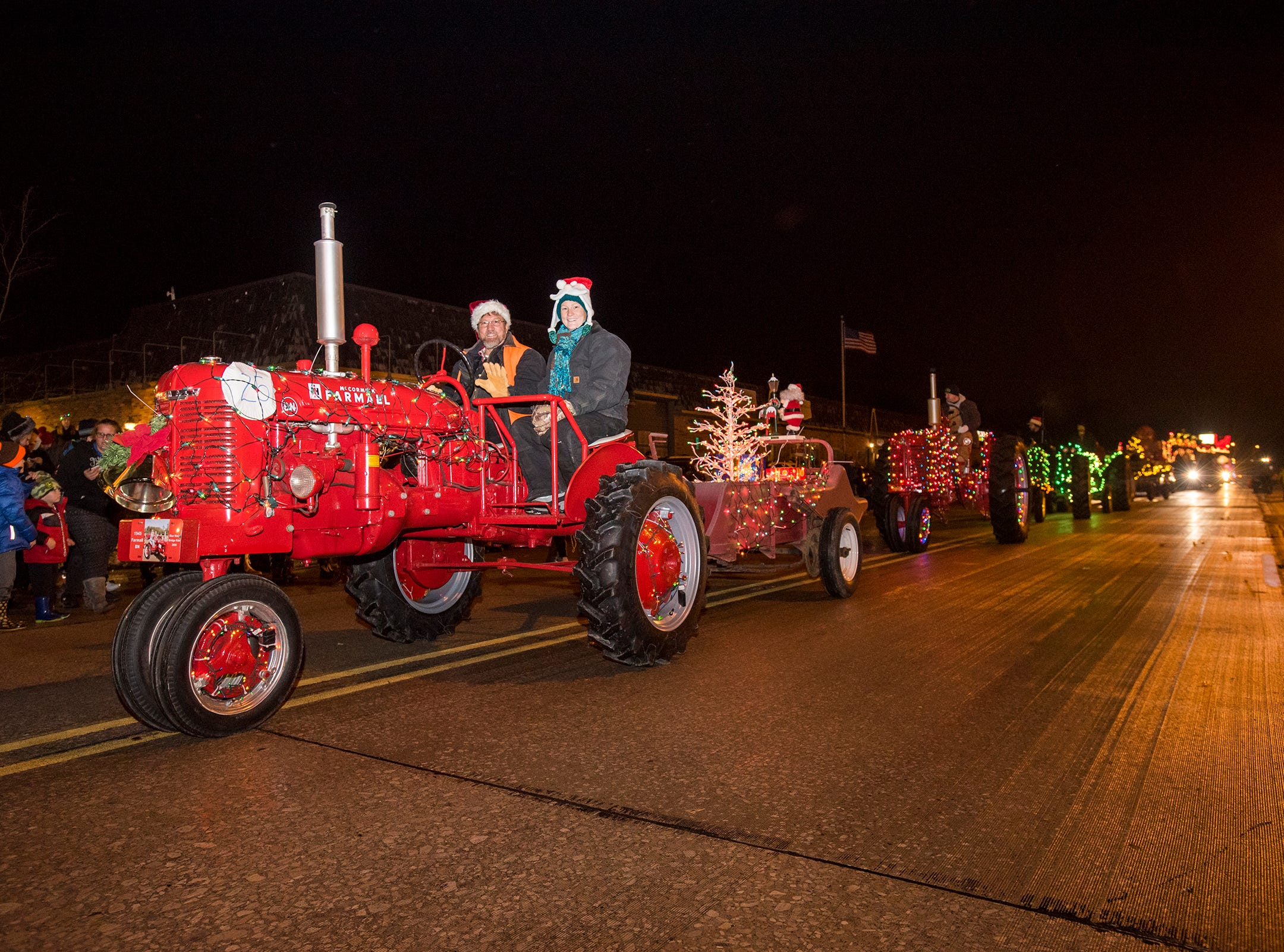 A line of antique tractors drive down Riverside Avenue Friday, Nov. 16, 2018 during the St. Clair Lighted Santa Parade.