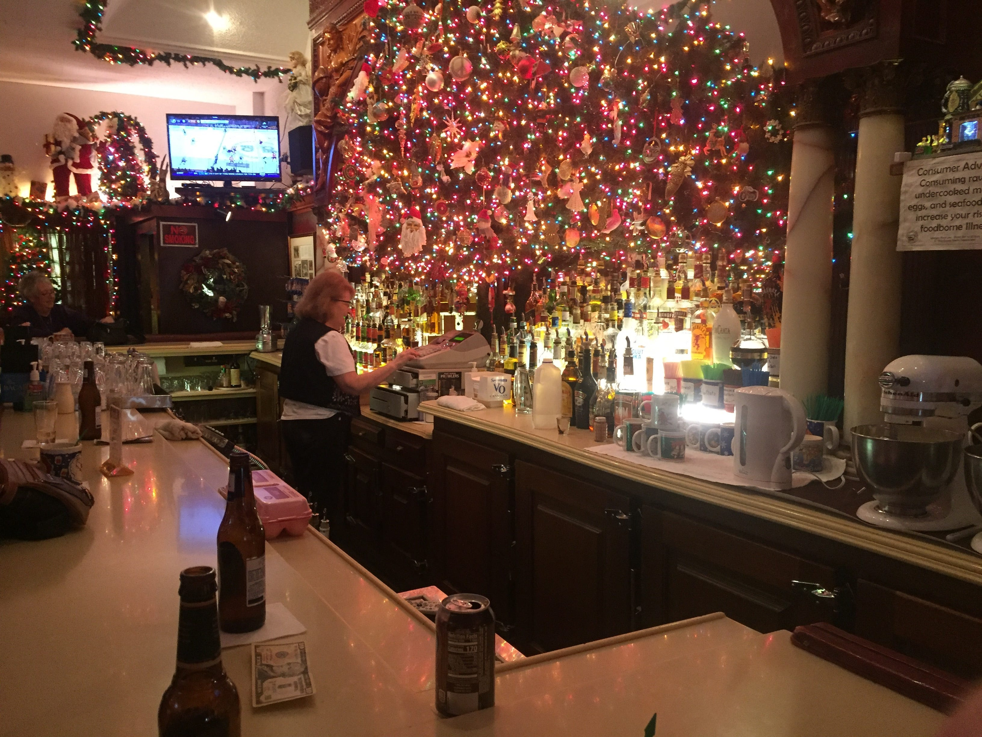 Sue Dunn is dwarfed by the large display of Christmas lights behind the bar at the Brass Rail.