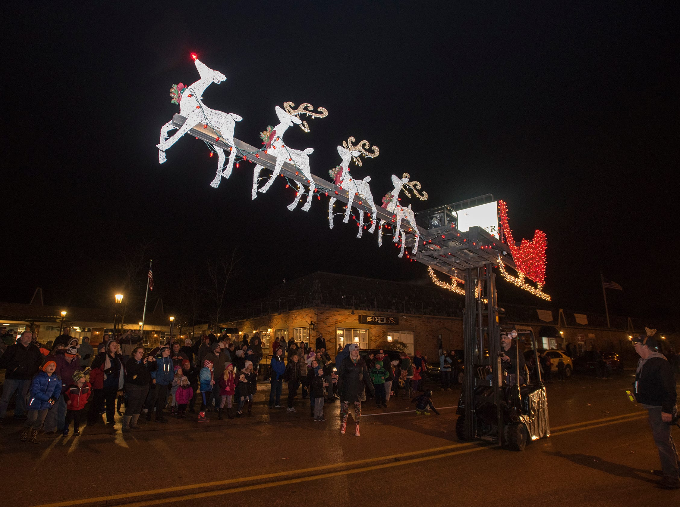 A forklift carries light-up reindeer and a sleigh from War Water Brewery down Riverside Avenue Friday, Nov. 16, 2018 during St. Clair's Lighted Santa Parade.