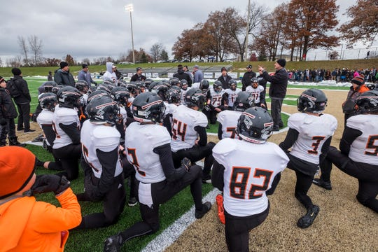 Marine City High School head coach Ron Glodich addresses the team in a huddle after the Mariners fell to Portland High School 35-14 in the MHSAA Division 5 state football semifinals Saturday, Nov. 17, 2018 at Howell High School.