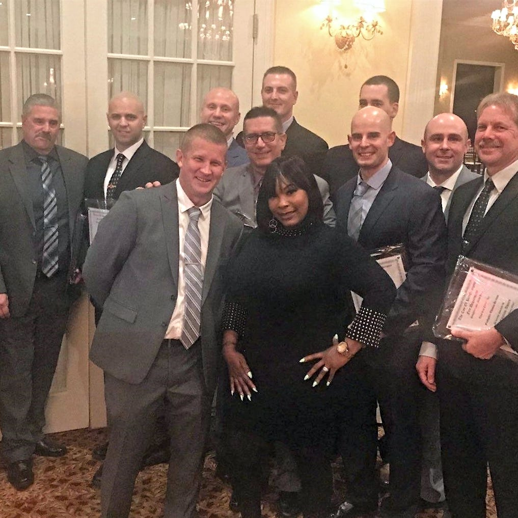 Rotanya Hargrove-Cooper, surrounded by the City of Poughkeepsie firefighters who helped save her from the rubble of a collapsed building. Hargrove-Cooper joined fire Chief Mark Johnson on Nov. 16, 2018, to present awards to 13  firefighters involved in her rescue.