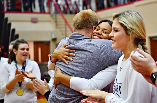 West York head coach Joe Ramp, left, hugs Alayna Harris, as he hands out first place medals to his team following a 3-0 win over Warren during PIAA 3A Girls' Volleyball Championship game action at Cumberland Valley High School in Mechanicsburg, Saturday, Nov. 17, 2018. Dawn J. Sagert photo