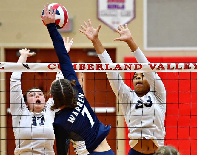 West York's Taylor Morley, left, and Alayna Harris, right, move to block as Warren's Jordan Sitler hits the ball across the net during PIAA 3A Girls' Volleyball Championship game action at Cumberland Valley High School in Mechanicsburg, Saturday, Nov. 17, 2018. West York would win the game 3-0. Dawn J. Sagert photo