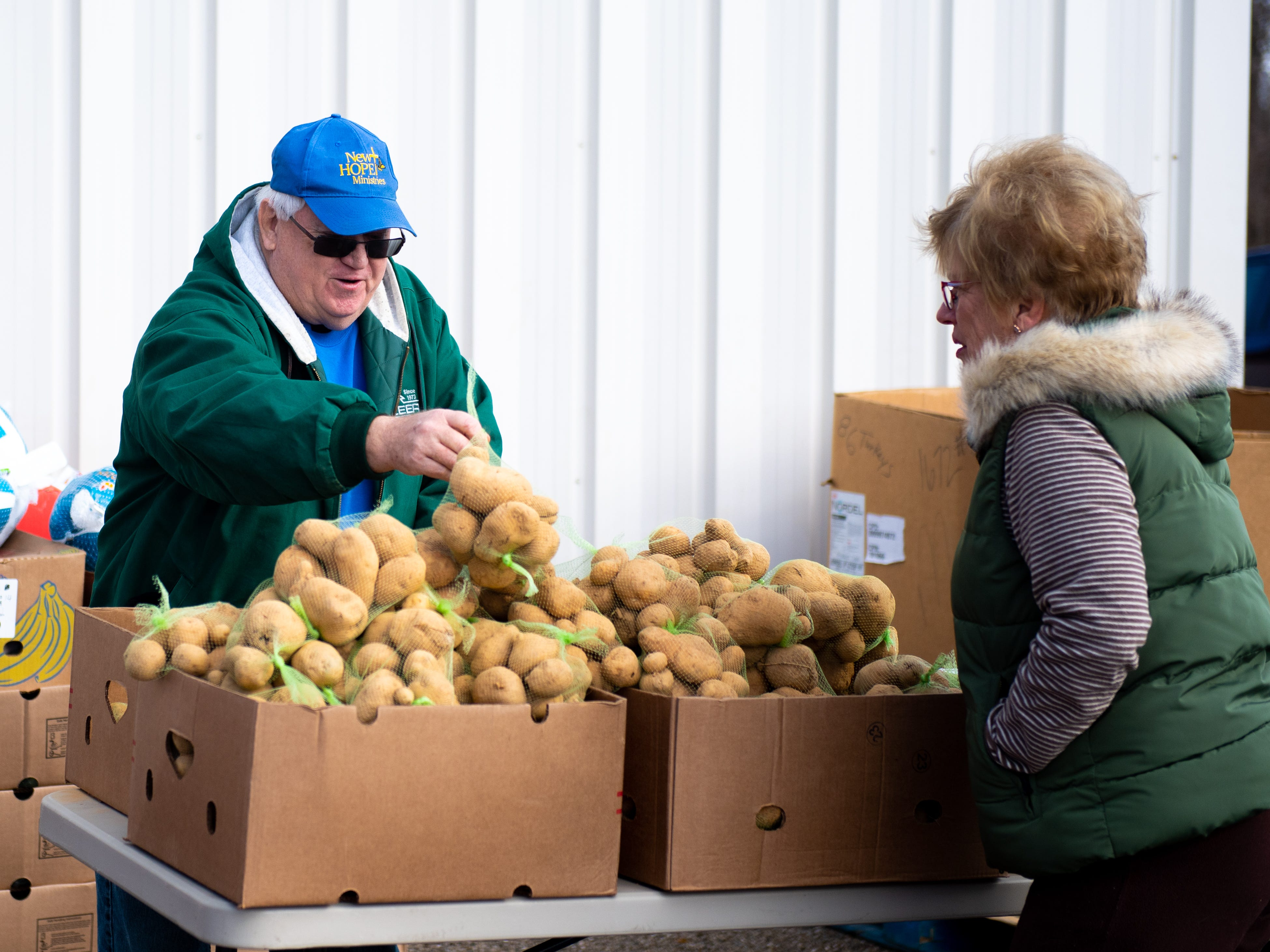 George Frank, left, assisted by Sandy Heff, refills the potato box during the Thanksgiving food giveaway provided recently by New Hope Ministries in Dover. The organization is just one of several groups around York County working to ensure everyone gets a traditional Thanksgiving dinner.