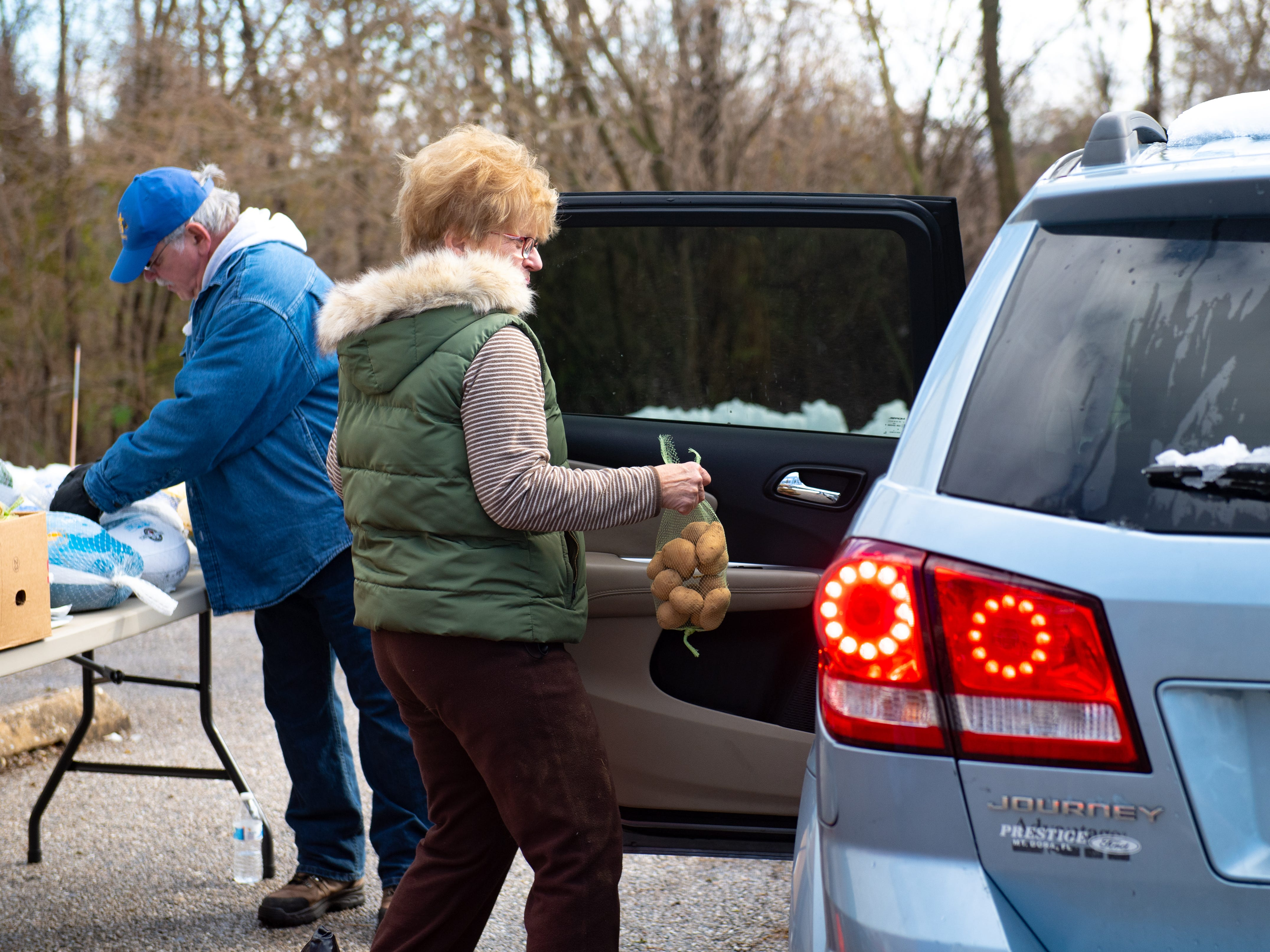 When guests pull around the back of the building, volunteers load their cars with food. Sandy Neff puts the potatoes in the back seat of the van during the Thanksgiving food giveaway provided by New Hope Ministries, November 16, 2018.