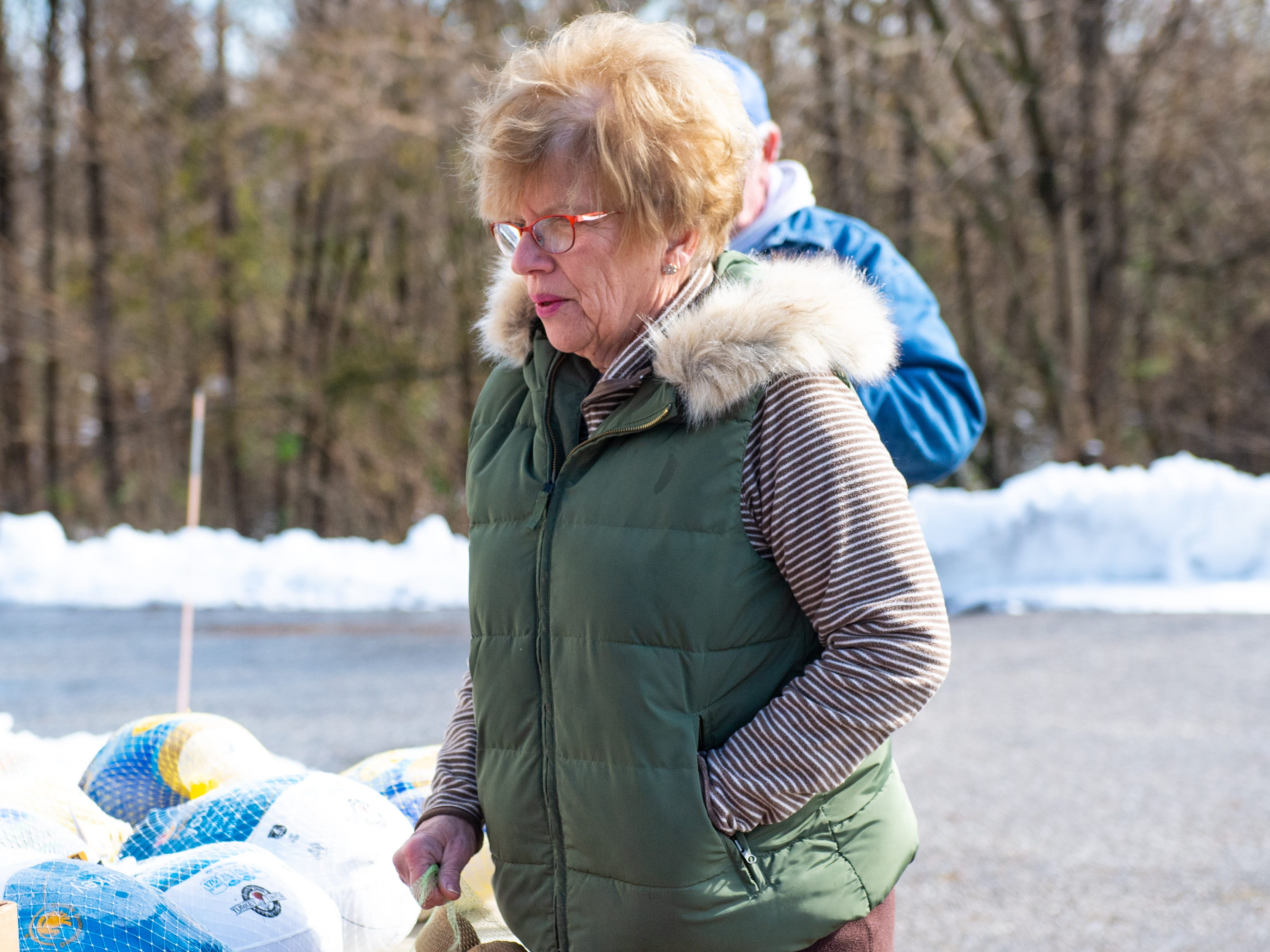 Sandy Neff waits for the next visitor to drive up, so she can hand them potatoes during the Thanksgiving food giveaway provided by New Hope Ministries, November 16, 2018.