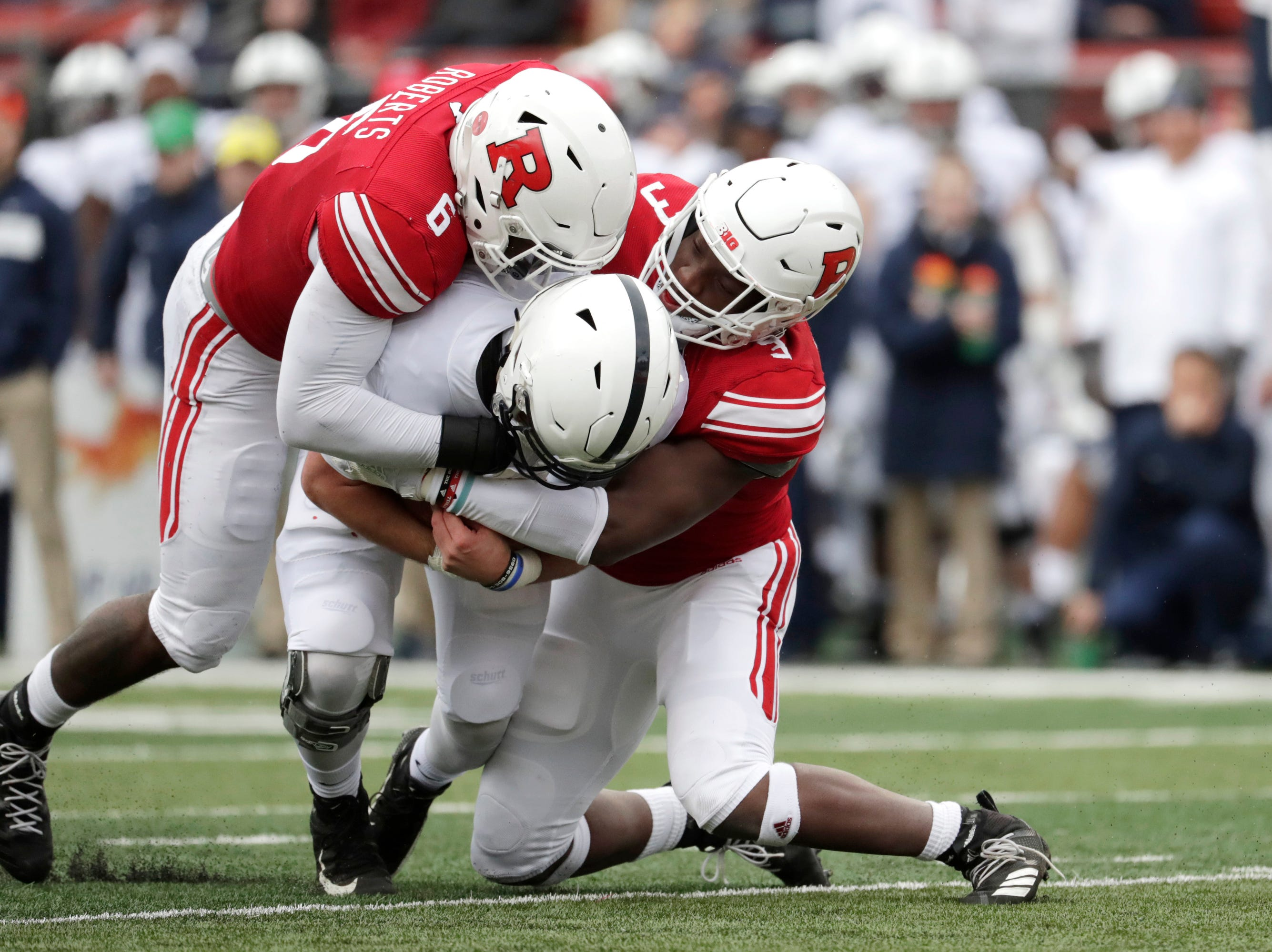 Penn State quarterback Trace McSorley, center, is tackled by Rutgers linebacker Deonte Roberts, left, and linebacker Olakunle Fatukasi during the first half of an NCAA college football game, Saturday, Nov. 17, 2018, in Piscataway, N.J. (AP Photo/Julio Cortez)