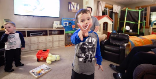 Coleson Harang, 3, puts up a peace sign as he plays in the living room of the Harang's New Salem home. The Harangs are a host family for York Catholic international students.
