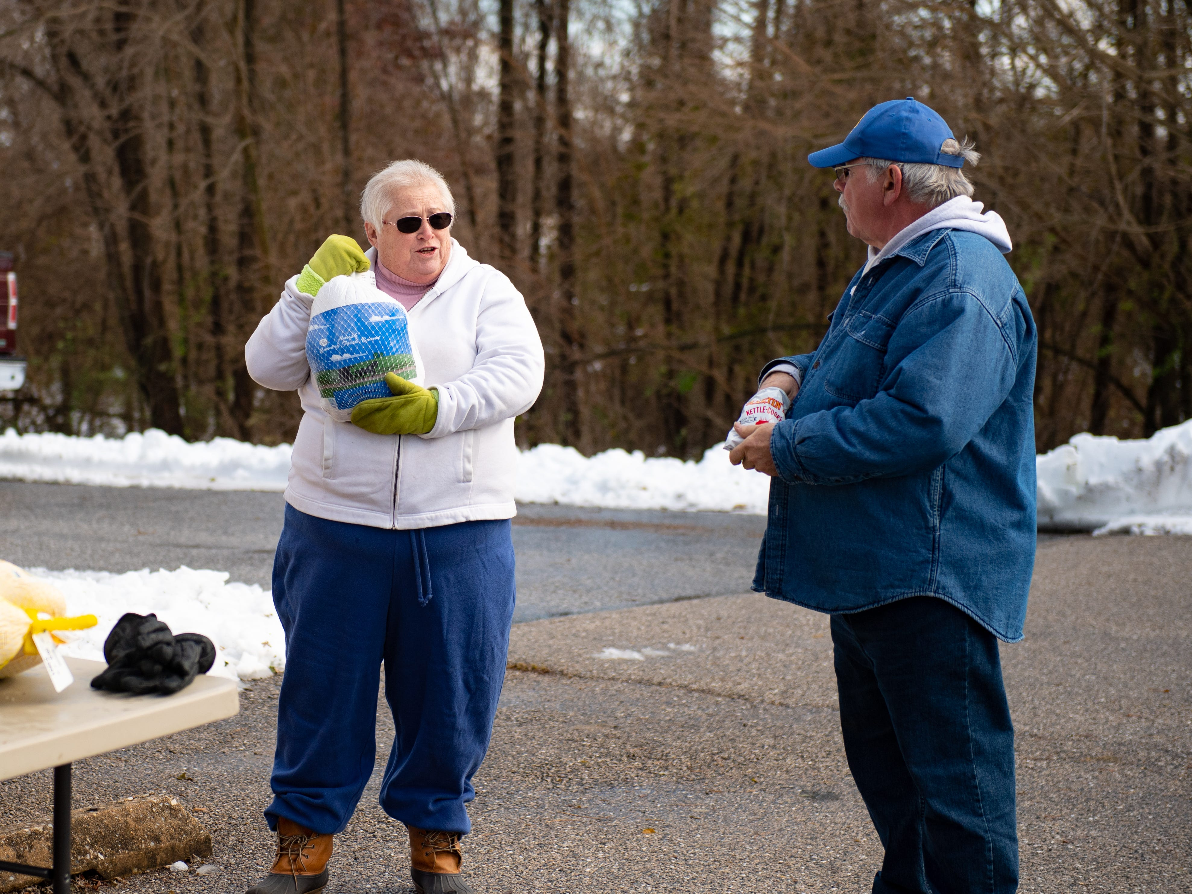 Carla Shermeyer shows Michael Neff the next turkey she'll hand out during the Thanksgiving food giveaway provided by New Hope Ministries, November 16, 2018.