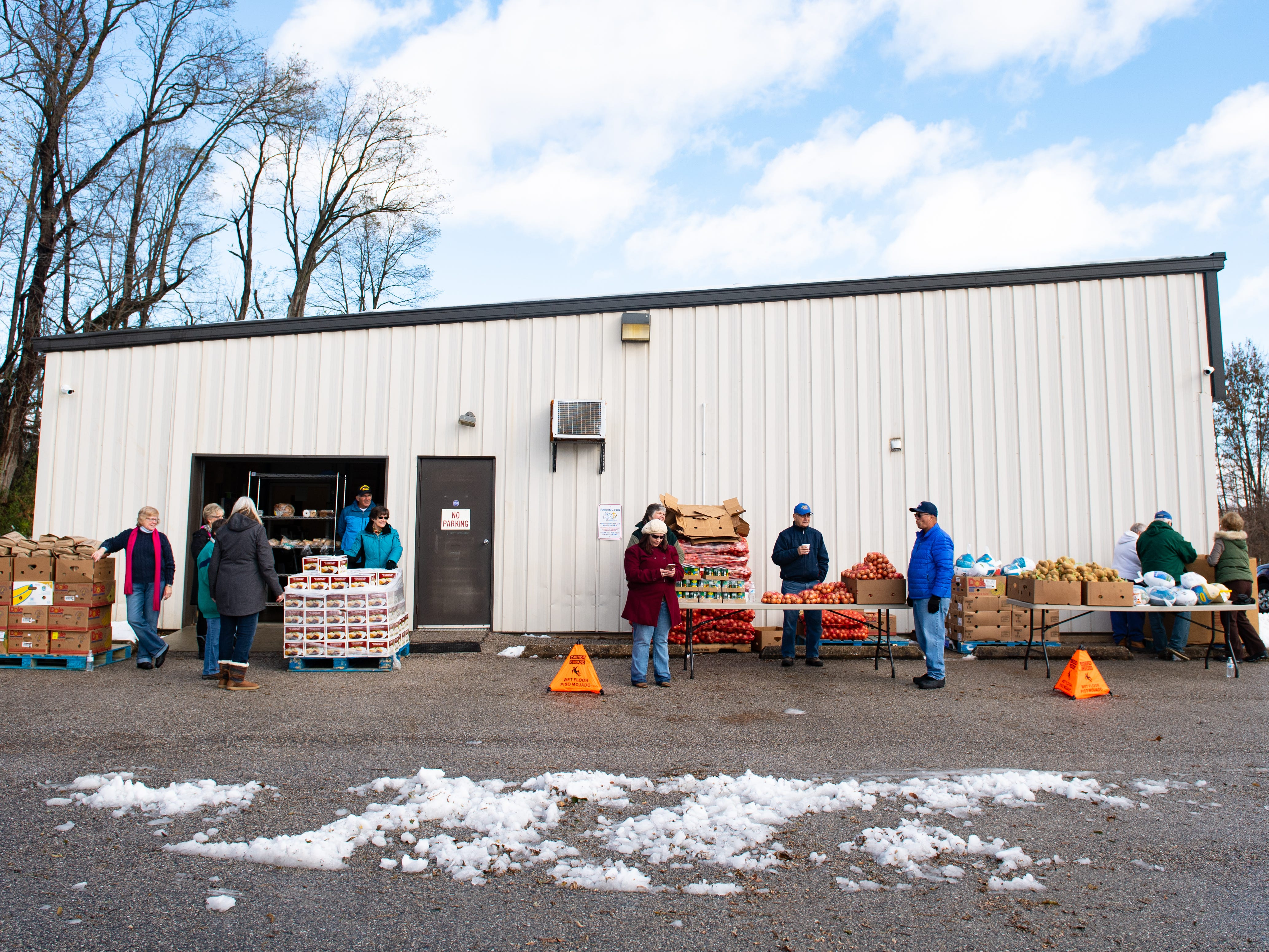 The Thanksgiving food giveaway was held at New Hope Ministries in Dover. Visitors drove around the building, and volunteers placed food in their vehicles as they passed by, like an assembly line.