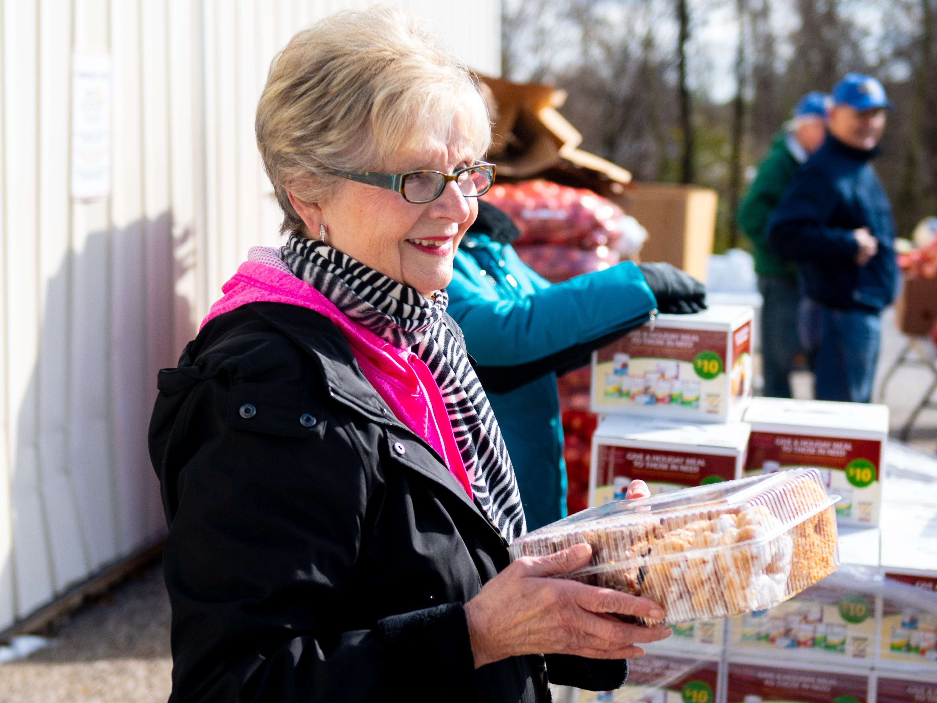 Bonnie Brodbeck brings out donuts during the Thanksgiving food giveaway provided by New Hope Ministries, November 16, 2018.